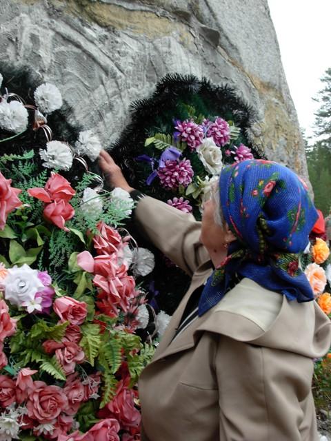 """Місцева мешканка покладає квіти до """"Соловецького каменя"""" з написом """"Люди, не убивайте друг друга!"""" Вона вшановує когось зі своїх рідних, що тут загинули. 2009 р."""