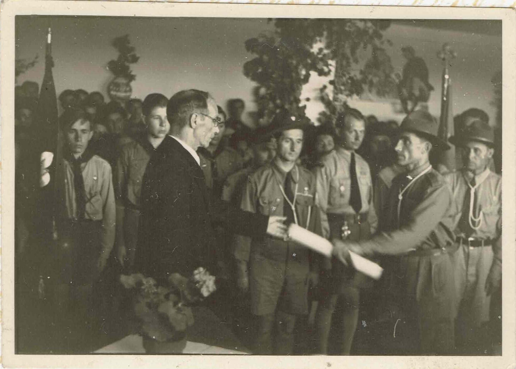 Пл.сен. Яро Гладкий, ЧМ, перебирає грамоту УСС для пластунів, 20.06.1948